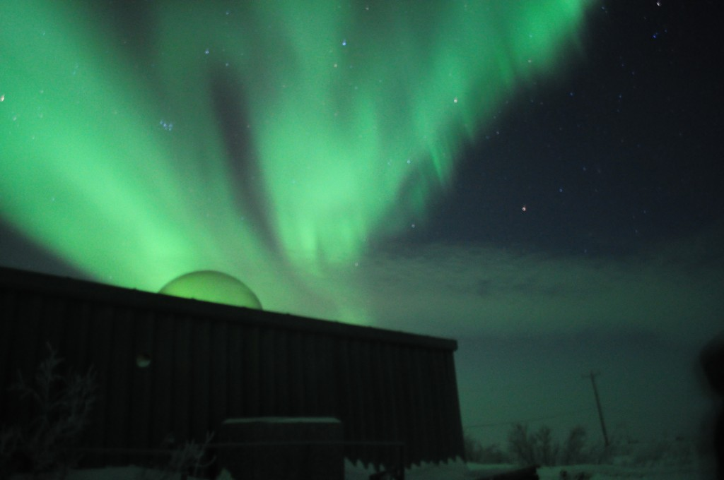 Aurora over the aurora domes in Churchill,MB
