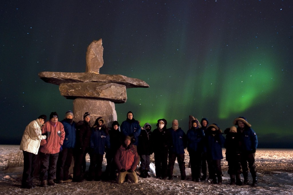 Ecstatic travelers take a group photo by the Hudson Bay.