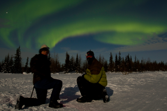 Photographers under the aurora borealis.
