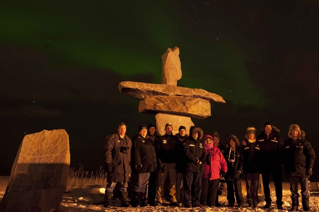 Inukshuk group photo with aurora over the bay. Colby Brokvist photo.
